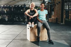 Smiling women sitting on a box together after working out