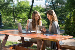 Smiling women sitting outdoors in park drinking coffee using laptop Stock Images