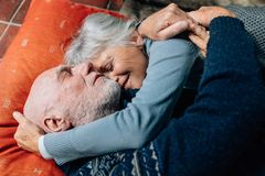 Senior couple expressing love embracing each other lying on floo royalty free stock image