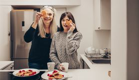 Smiling women standing in kitchen holding cookies royalty free stock photos