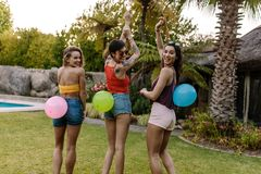 Group of friends playing balloon pop game. Smiling women standing outdoors with balloons tied on their back. Group of friends enjoying balloon pop game at party royalty free stock image