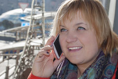 Smiling women at the street. The smiling woman calling by phone at the street royalty free stock photo