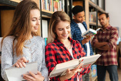 Smiling women students standing in library reading books. Stock Photos