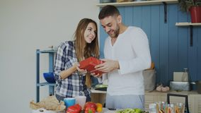 Cheerful woman surprising his boylfriend with birthday gift at home in the kitchen while he cooking breakfast. Smiling women surprising his boylfriend with Royalty Free Stock Image