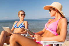 Smiling women with tablets pc computers on beach Stock Photos