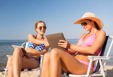 Smiling women with tablets pc computers on beach Stock Photography