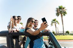 These Are The Crazy Memories We`ll Look Back On. Smiling women taking selfie with besties in 4x4 vehicle at beach stock image