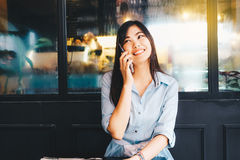 Smiling women talking on smart phone in cafe Stock Photo