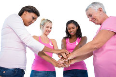 Smiling women wearing breast cancer ribbons putting hands togeth Stock Images