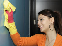 Smiling women worker cleaning the house - wardrobe. A casual girl using a disinfectant wipe to clean the wardrobe Stock Images