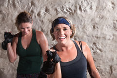 Smiling Women Working Out. Smiling women with workout partner lifting weights Stock Photos