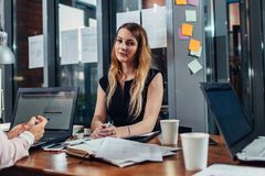 Smiling woman working sitting in modern office Royalty Free Stock Photography
