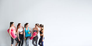 Smiling women yoga / fitness class. Young athletic women friends with yoga mats and dumbbells on a white background stock images