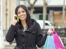 Smiling wonan talking by phone and holding shopping bags. Royalty Free Stock Photo