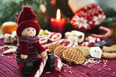Smiling wooden doll with sweets on christmas background. Wooden smiling doll with sweets on christmas background. Closeup Royalty Free Stock Image