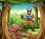 A smiling woodman holding an axe in the middle of the forest Stock Photos