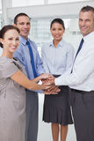 Smiling work team joining hands together Royalty Free Stock Images