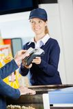 Smiling Worker Accepting Payment Through NFC Royalty Free Stock Images