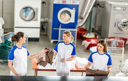 Smiling worker adds ironed linens. Smiling worker ads ironed other textile workers stock photography