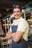Smiling worker in apron with arms crossed Royalty Free Stock Photos