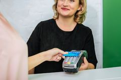 Blonde-haired worker of beauty salon smiling while contacting with client royalty free stock image