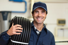 Smiling worker carrying corrugated conduit and a tester Stock Images