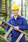 Smiling Worker Carrying Ladder At Construction. Portrait of smiling male worker carrying ladder at construction site Stock Photos