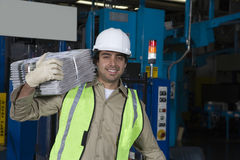 Smiling Worker Carrying Newspapers In Factory Stock Photo