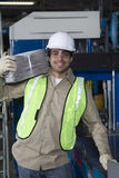 Smiling Worker Carrying Newspapers In Factory Royalty Free Stock Image