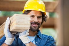 Smiling Worker Carrying Tied Wooden Planks Stock Photo
