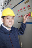 Smiling worker checking controls in a gas plant, Beijing, China, looking at camera, portrait Stock Images