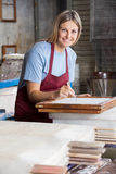 Smiling Worker Cleaning Paper With Tweezers Royalty Free Stock Image