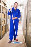 Smiling worker cleaning warehouse with mop Royalty Free Stock Photo