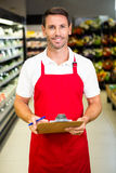 Smiling worker with clipboard. In grocery store Royalty Free Stock Photography