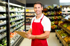 Smiling worker with clipboard. In grocery store Stock Photos