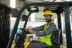 Smiling worker driving a forklift car in factory. Portrait of smiling worker driving a forklift car in factory royalty free stock photography