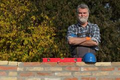 Smiling worker examining brick wall. Smiling worker or engineer control brick wall using level tool, real people, no retouch Royalty Free Stock Photo