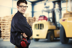 Smiling worker in front of forklift Royalty Free Stock Photos