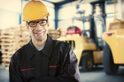 Smiling worker in front of forklift Stock Photo