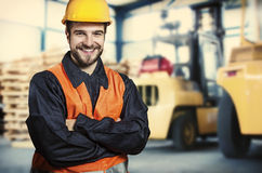 Smiling worker in front of forklift Royalty Free Stock Photography