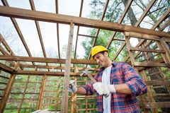 Smiling Worker Hammering Nail On Timber Cabin Royalty Free Stock Photography
