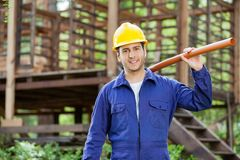 Smiling Worker Holding Pipe At Construction Site Stock Photo