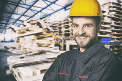 Free Smiling Worker In Protective Uniform In Front Of Wooden Pallets Royalty Free Stock Photos - 65329298