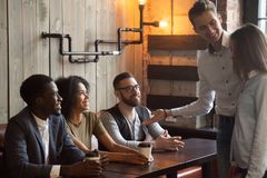 Smiling worker introducing new employee to colleagues during caf. Smiling Caucasian boyfriend introducing multiracial friends to girlfriend at meeting in stock image