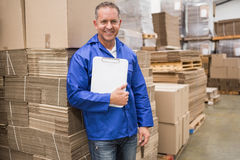 Smiling worker leaning on pile of cardboard Stock Image