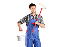 Smiling worker man holding a paint roller. And bucket isolated on white background Stock Photos