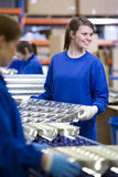 Smiling worker moving aluminium light fittings in factory Royalty Free Stock Image