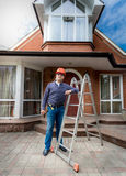 Smiling worker posing against beautiful newly built house Royalty Free Stock Photography