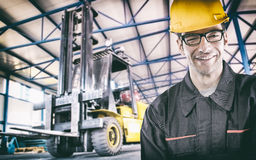 Smiling worker in protective uniform in front of forklift Royalty Free Stock Images