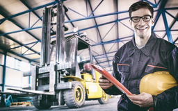 Smiling worker in protective uniform in front of forklift. Smiling worker in protective uniform in production hall in front of forklift - toned image, retro film Stock Photography